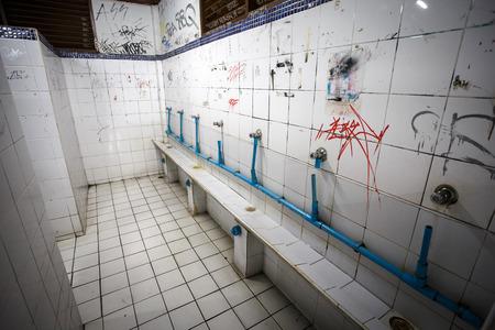 ghetto: Urinal in an urban ghetto washroom  restroom with dirty grungy graffiti walls