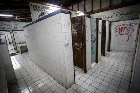 ghetto: An urban ghetto washroom  restroom with dirty grungy graffiti walls Editorial