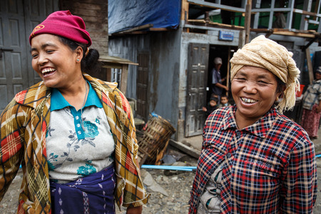 foreigners: CHIN STATE, MYANMAR - JUNE 23 2015: Friendly ladies in village popular for selling apples in the recently opened to foreigners area of Chin State - western Myanmar (Burma)