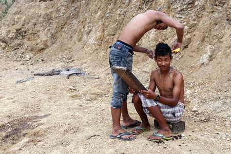 foreigners: FALAM, MYANMAR - JUNE 17 2015: Local young men cut hair in the recently opened to foreigners area of Chin State - western Myanmar (Burma) Editorial