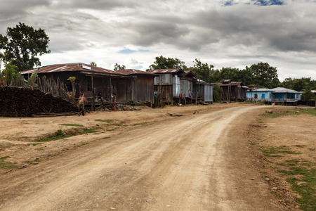 monsoon clouds: Dirt road leading through village in  Chin State in Myanmar (Burma)