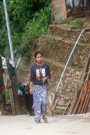 chins: CHIN STATE, MYANMAR - JUNE 18 2015: Lady walking through Falam Town in the recently opened for tourists Chin State Mountainous Region, Myanmar (Burma)