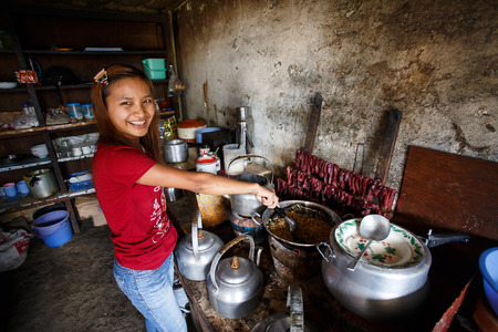 food state: CHIN STATE, MYANMAR - JUNE 18 2015: Cute girl cooks traditional food in the recently opened for tourists Chin State Mountainous Region, Myanmar (Burma)