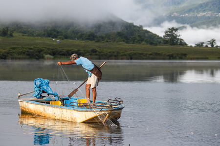 fibreglass: RHI LAKE, MYANMAR - JUNE 21 2015: Local fisherman on the daily fishing trip at the start of the monsoon season in the recently opened to tourists Chin State region of Western Myanmar (Burma)