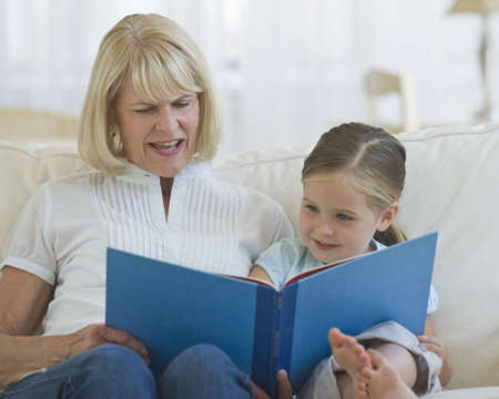 grand daughter: Grandmother reading a book to her grand daughter