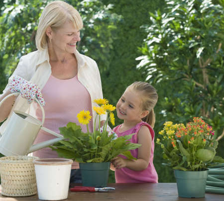 watering plants: Grandmother and grand daughter watering plants Stock Photo