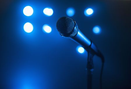 A close up view of a microphone and stand.  The background is blue and has several spotlights. Horizontally framed shot. Stock Photo - 5379877