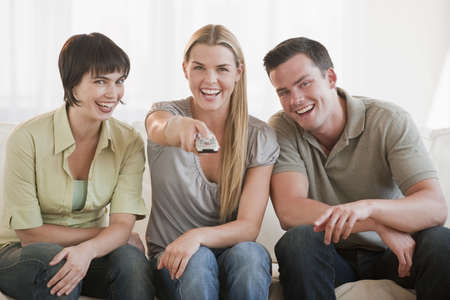 they are watching: A group of three friends are sitting on a couch together and watching TV.  They are smiling at the camera.  Horizontally framed shot. Stock Photo