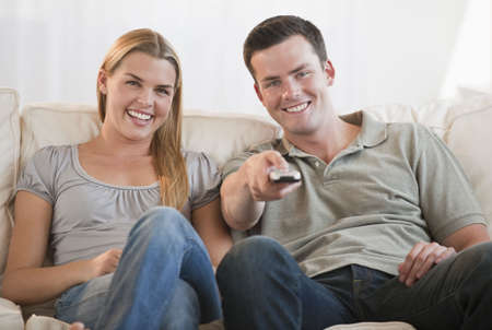 they are watching: A happy young couple watching TV together.  They are smiling, and the man is holding a remote control.  Horizontally framed shot.