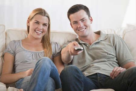 pareja viendo tv: Una joven pareja de ver la tele juntos. Est�n sonriendo, y el hombre se mantiene un control remoto. Horizontalmente enmarcada disparo. Foto de archivo