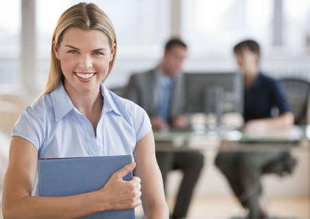 expert comptable: Une femme jeune et belle en souriant � la cam�ra � son offce. Il ya deux personnes qui travaillent dans l'ombre. Horizontalement framed shot.