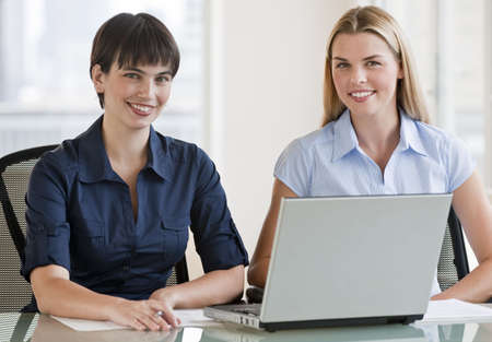 midlife: Two beautiful women working on a computer together.  They are smiling directly at the camera. Horizontally framed shot. Stock Photo