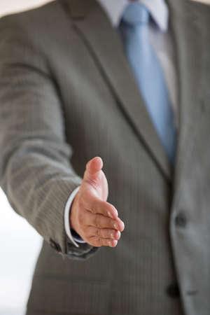 extending: A businessman is extending his hand for a handshake.  Vertically framed shot.