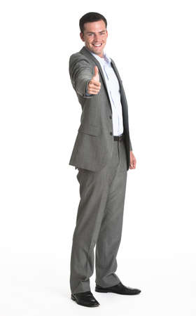 midlife: A businessman making a thumbs up gesture.  He is smiling at the camera.  Vertically framed shot.