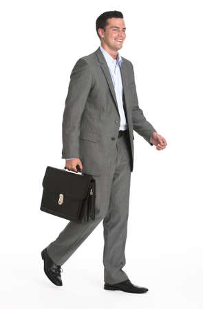 midlife: A young businessman is walking and holding a briefcase.  He is smiling and looking away from the camera.  Vertically framed shot. Stock Photo
