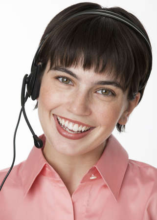 midlife: A young woman wearing a headset is smiling at the camera.  Vertically framed shot.