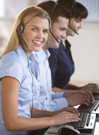 midlife: A group of people are typing on keyboards and wearing headsets.  The young woman is smiling at the camera.  Vertically framed shot. Stock Photo