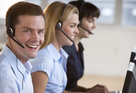 pc: Two female and one male customer service representatives smiling.  They are working on computers and are wearing headsets. The male is looking directly at the camera. Horizontally framed shot.