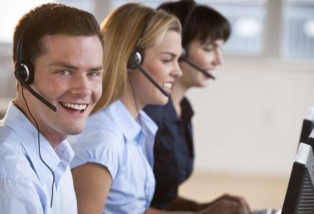 computer service: Zwei weibliche und eine m�nnliche Kundendienstmitarbeiter l�chelnd. Sie arbeiten an Computern und tragen Headsets. Der Mann ist direkt auf die Kamera. Horizontal framed shot.