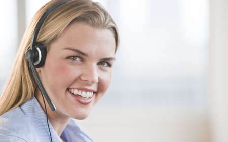midlife: A beautiful young female smiling with a headset on.  Horizontally framed shot.
