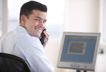 An attractive business man working on a computer and talking on a cellphone.  He has a bar chart on his computer screen and is smiling at the camera.  Horizontally framed shot. photo