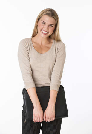 midlife: A young woman is holding onto a notebook.  She is smiling at the camera.  Vertically framed shot.