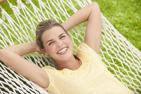 An attractive young female relaxing outside in a hammock.  She is smiling.  Horizontally framed shot. Stock Photo
