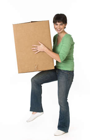 A woman is holding a moving box and smiling at the camera.  Vertically framed shot. photo