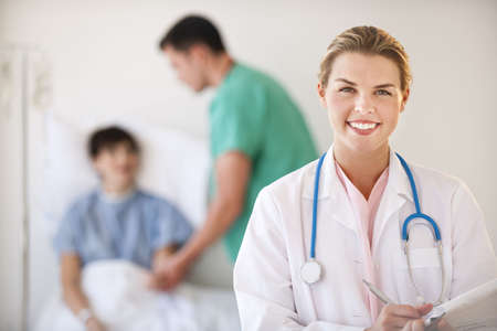 horizontally: A young female doctor is smiling at the camera while a male nurse helps a patient in the background.  Horizontally framed shot. Stock Photo
