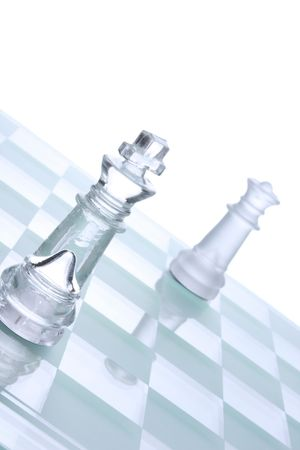 Translucent glass chess figures on a board Stock Photo