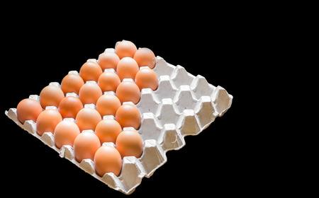 黒の背景に分離されたパッケージで鶏から卵