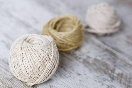 Natural fiber rope balls over a wooden background