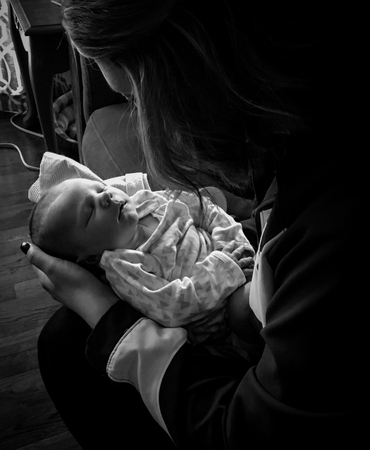Peaceful image of mother holding  newborn baby on the first day home from the hospital. Excellent for Mothers Day use, womens rights articles, planned parenthood, adverts