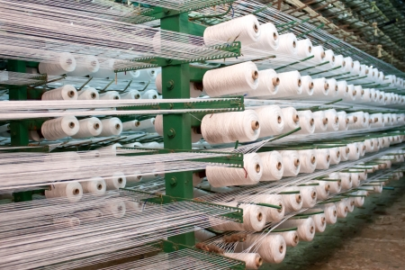 the textile industry: large group of bobbin thread cones on a warping machine in a textile mill  Stock Photo