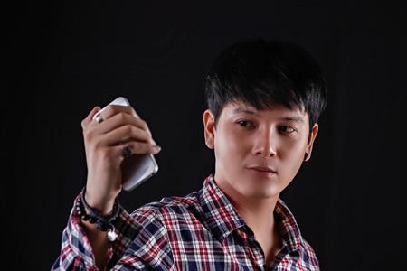 stylish hair: Portrait of Asian young man on black background