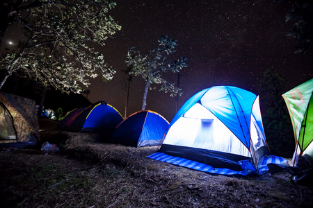 Night camping, glowing tent in the forest