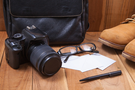 Travel concept - Leather bag, glasses, shoe, paper, pen, camera on wooden desk Stock Photo