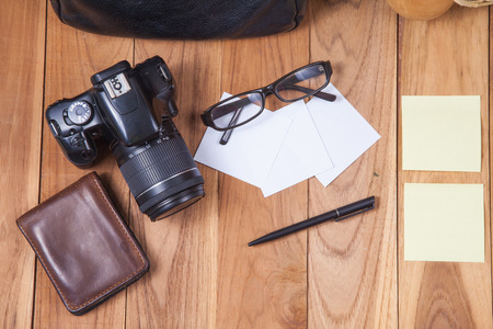 Travel concept - Leather bag, glasses, shoe, paper, pen, camera, wallet on wooden desk Stock Photo