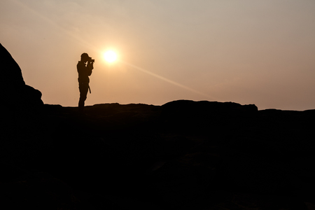 silhouette of a traveler who shoots a sunset in the mountains