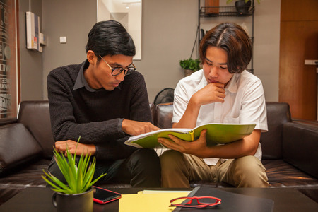 Young tutor teaching student in the coworking space ; Education concept