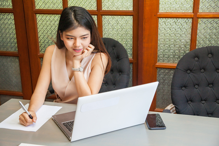 Beautiful Asian young girl work in coworking space with laptop
