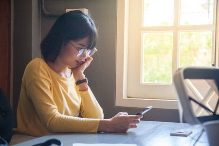 Young Asian lady use smartphone in coworking space Stock Photo