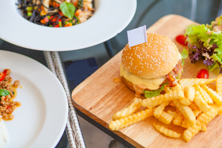 Pork bacon cheese burger with potato fried and vegetable on wood plate Stock Photo