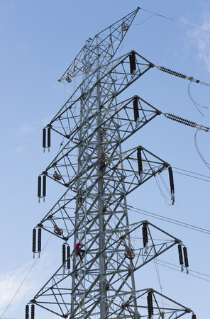 structuring: the workers are structuring high voltage electricity pylon.