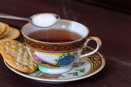 antique table: Antique tea cup full of tea with sugar and crackers on wooden table Stock Photo
