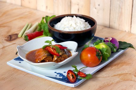 fish sauce: Sardines fish in tomato sauce with cooked rice on wooden table
