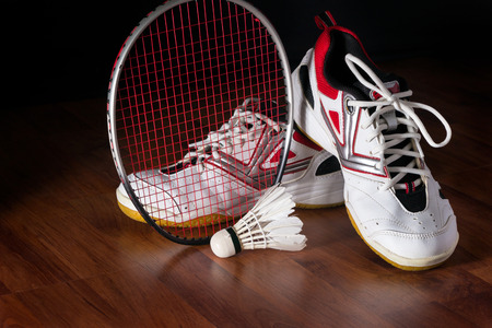 badminton: Shuttlecock, badminton racket and shoe on wooden background