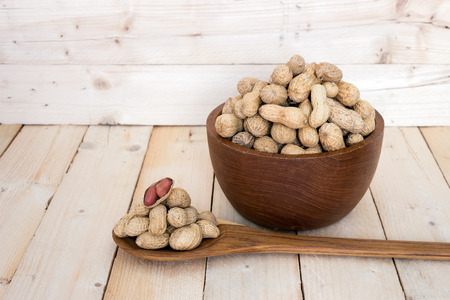 monkey nuts: Peanuts in wooden bowl on wooden background Stock Photo