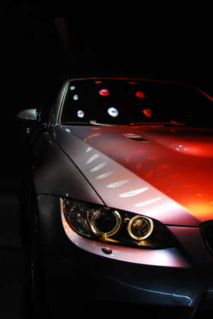 luxery: A car sits in a dark room under a series of lights. Stock Photo