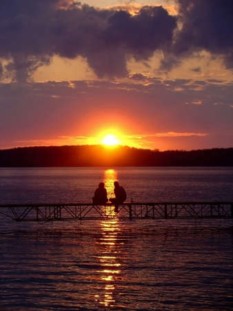A man and a woman sit and watch the sunset on Lake Mendota, WI.